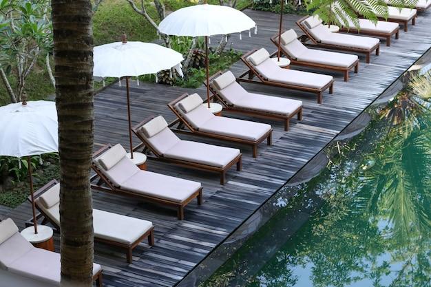 Bella piscina a sfioro in un giardino tropicale, un'area relax per turisti con lettini e ombrelloni, riflesso delle palme nell'acqua, bali, indonesia
