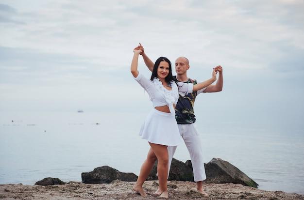 Belle coppie infiammatorie che ballano sulla spiaggia