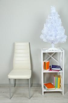 Bellissimi interni con sedia moderna a colori, libri su supporto in legno, sullo sfondo della parete