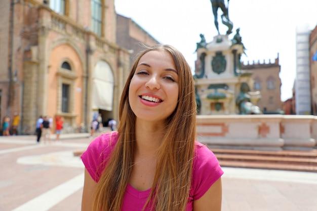 Bella italia. ritratto di bella ragazza sorridente in piazza del nettuno, città di bologna, italia.