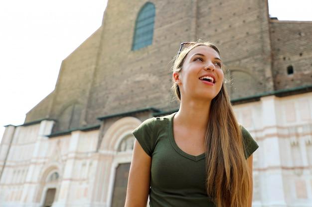 Bella italia. donna abbastanza giovane turista nella città medievale di bologna con la basilica di san petronio sullo sfondo. concetto di turismo italiano.