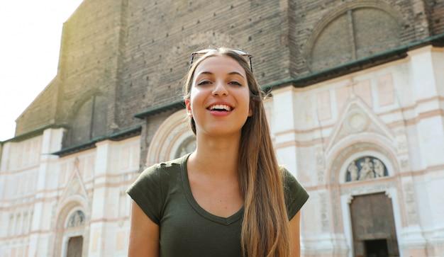 Bella italia. donna abbastanza giovane turista nella città medievale di bologna con la basilica di san petronio sullo sfondo.