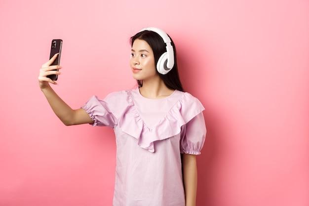 Bella ragazza giapponese prendendo selfie sullo smartphone, indossando le cuffie wireless, in piedi su sfondo rosa.
