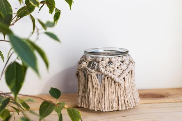 Bellissimo portacandele in vaso con decoro macramè su mensola in legno. decorazioni per la casa boho. pianta d'appartamento di fronte. decorazione rustica.