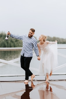 Bellissimi appena sposati ballano a piedi nudi e si divertono sul molo in riva all'acqua.