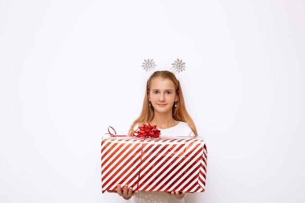 Una bella ragazza del bambino che tiene una scatola regalo a strisce rossa di natale con un nastro e un fiocco in mano. ci sono fiocchi di neve sulla testa. isolato