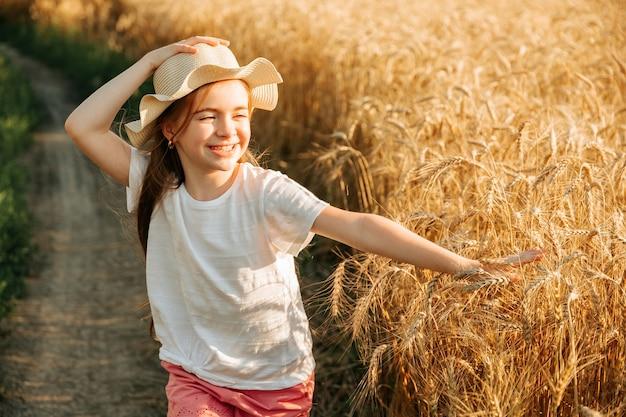 Bella bambina con cappello in testa e sorriso attraente corre sulla strada di campagna vicino al campo...