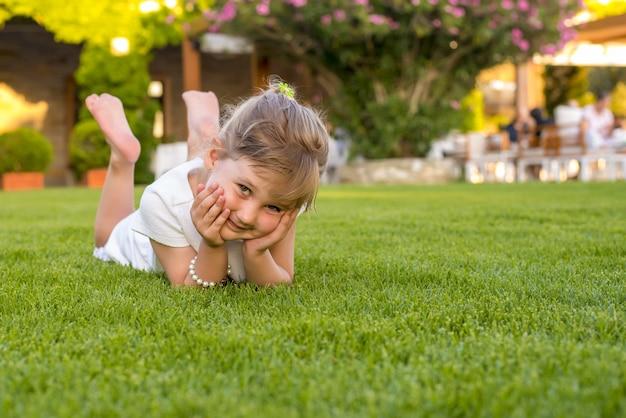 Bel bambino in posa sull'erba nel parco
