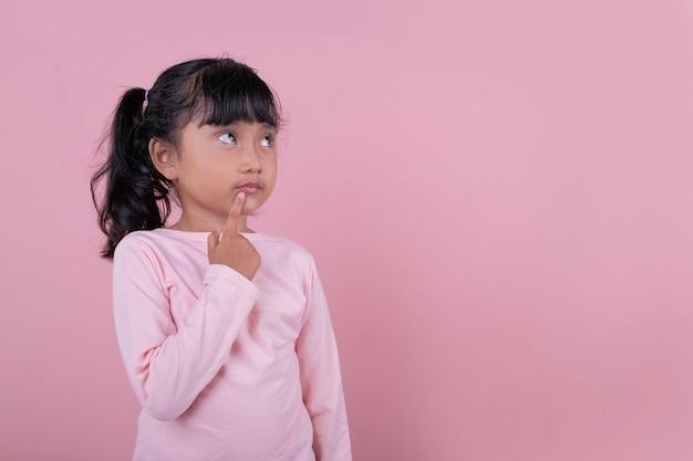 Un bellissimo bambino che ottiene una nuova idea indossando una maglietta rosa tenue