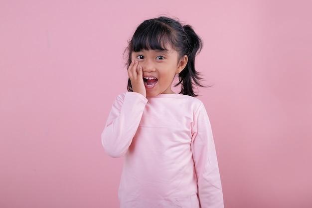 Un'espressione scioccata dei bei bambini che porta la maglietta rosa tenue