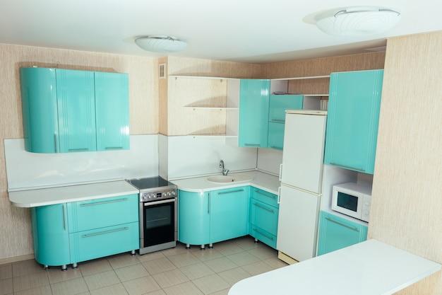 Bella cucina dai colori turchesi con frigorifero, microonde, tavolo, fornelli e lavello
