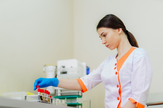 La bella donna del tecnico di laboratorio in uniforme medica lavora con i campioni di sangue.