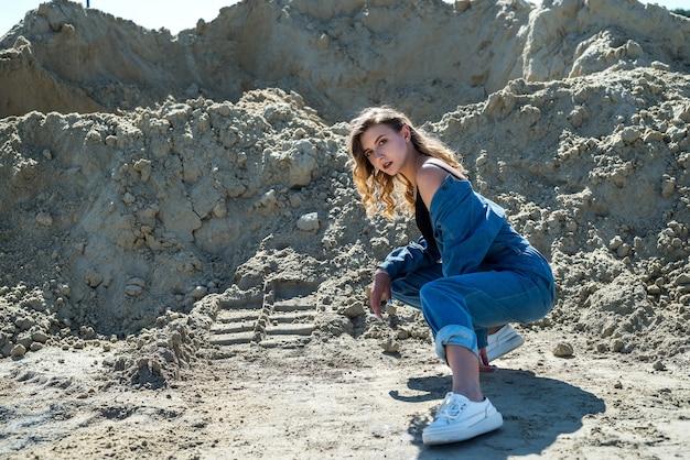 La bella signora in tuta blu cammina in una cava di sabbia, in modo attivo