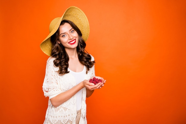 Bella signora godersi il tempo di vacanza tenendo lampone fresco che indossa il cappello di pamela