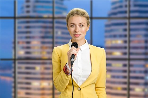 Bella signora che tiene il microfono. mezzo busto ritratto di reporter donna elegante in piedi la sera in ufficio e sorride alla macchina fotografica.