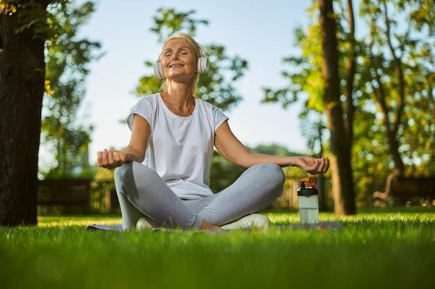 Bella signora in abbigliamento sportivo seduta su un tappetino da yoga e meditando mentre si gode le canzoni preferite all'aperto