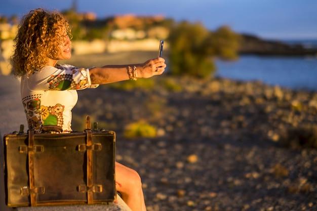Bella signora che scatta foto selfie con lo smartphone dopo il viaggio per le vacanze. sorridendo e godendosi la destinazione del mare. vecchi bagagli vintage per il concetto di voglia di viaggiare. spiaggia e luogo di mare
