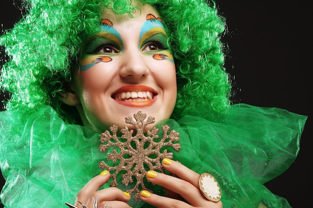 Bella signora con trucco artistico che tiene le decorazioni di natale. stile bambola.