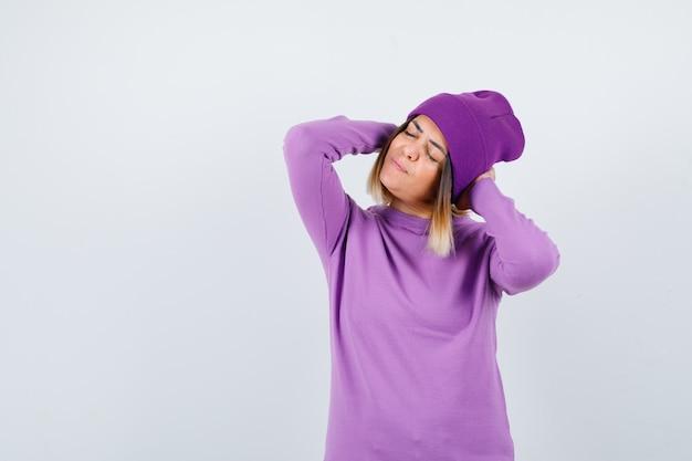 Bella signora con le mani dietro la testa, chiude gli occhi in maglione, berretto e sembra stanca. vista frontale.