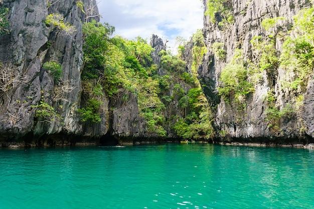 Bellissima laguna con acque turchesi cristalline circondata da alte scogliere sull'isola di palawan filippine