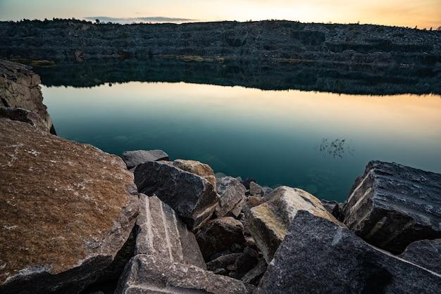 Bellissimo lago circondato da grandi mucchi di rifiuti di pietra dal duro lavoro in una miniera contro un bellissimo cielo notturno con le stelle