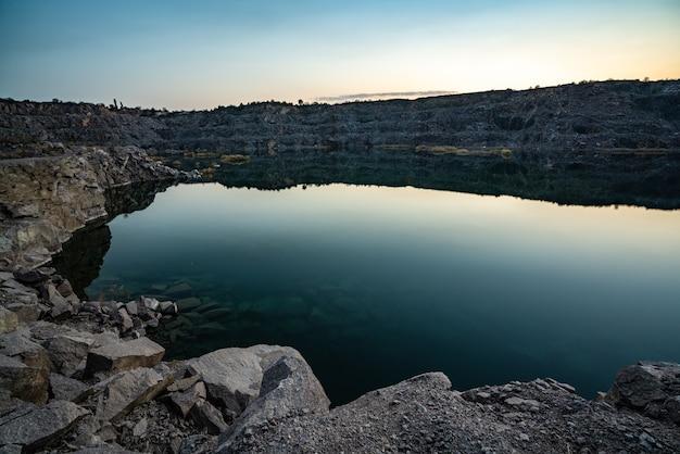 Bellissimo lago circondato da grandi cumuli di rifiuti di pietra dal duro lavoro in una miniera contro un bellissimo cielo notturno con le stelle