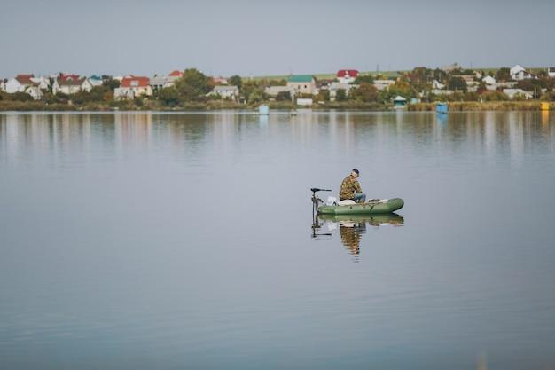 Il bellissimo pescatore di paesaggi si siede in giacca mimetica su gommone in mezzo al lago su sfondo di case in giornata di sole. stile di vita, ricreazione, concetto di svago dell'uomo. copia spazio per la pubblicità.