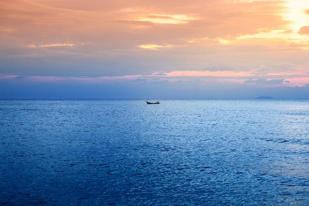 Barca solitaria di bellissimo paesaggio nel mare blu al tramonto