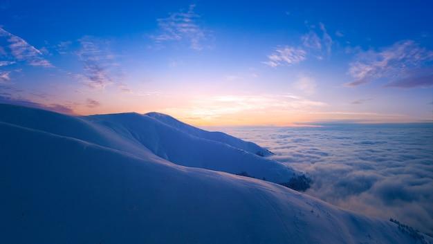 Bellissimo paesaggio, mare di nebbia, cime innevate e cielo nuvoloso e vista sulle montagne.