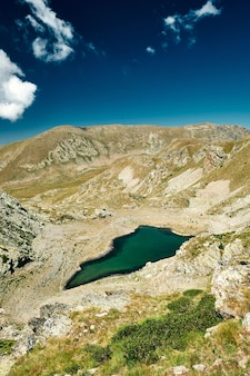 Bellissimo paesaggio di un piccolo lago circondato da una catena montuosa in una valle della costa azzurra