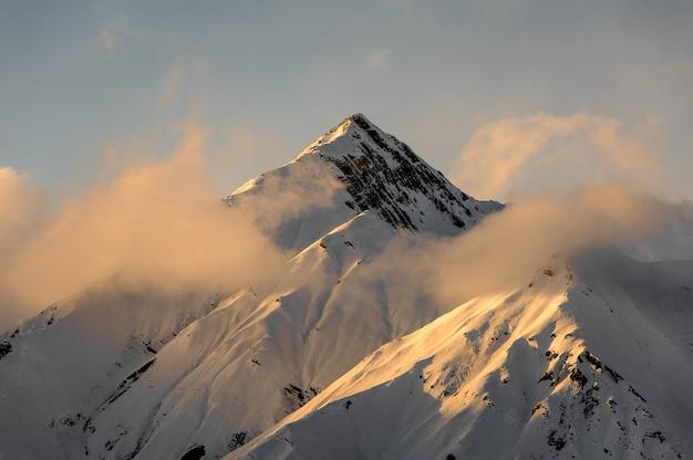 Bellissimo paesaggio della cima di una montagna innevata con foschia rosa chiaro intorno