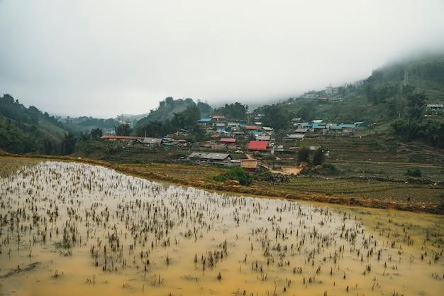 Splendide vedute del paesaggio delle terrazze di riso durante l'inverno fuori stagione con acqua fangosa nei campi.