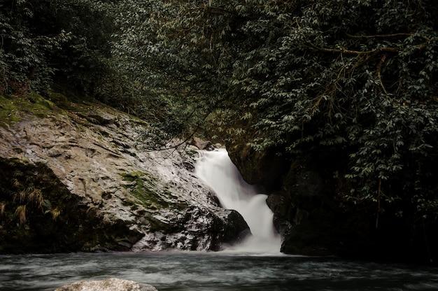 Bellissimo paesaggio dell'acqua che cade nel lago circondato dalle rocce nei bagni di afrodite in georgia