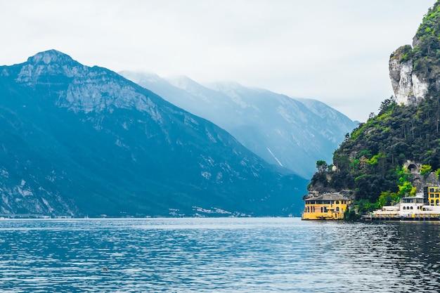Bellissimo paesaggio con casetta gialla vicino al lago di garda sullo sfondo delle montagne alpine.
