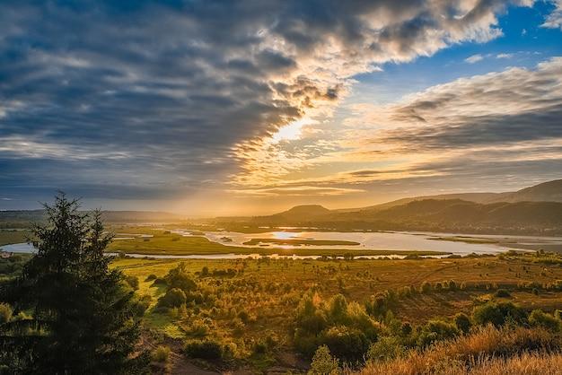 Bellissimo paesaggio con montagne e colline, fiume e alberi illuminati dai raggi del sole nascente