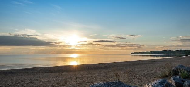 Bellissimo paesaggio con riflessi, cielo azzurro e luce solare gialla all'alba