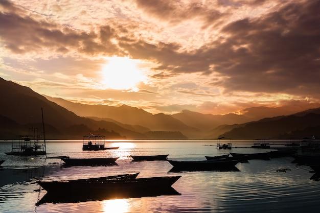 Bellissimo paesaggio con sole al tramonto sul lago pheva nella città di pokhara, nepal. barche alla luce del tramonto