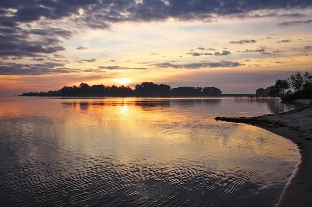 Bellissimo paesaggio con cielo e lago infuocati al tramonto. composizione della natura