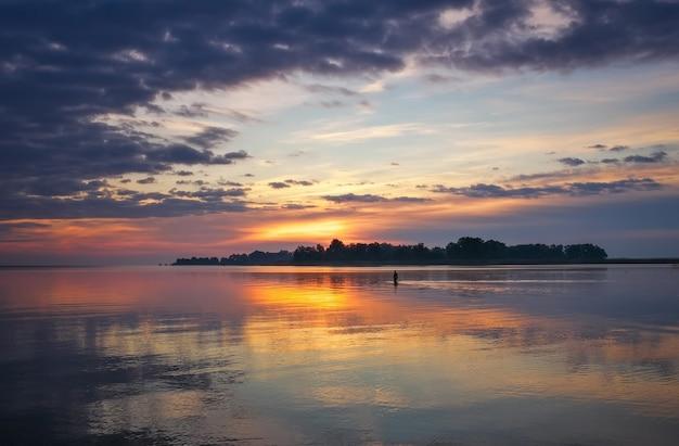 Bellissimo paesaggio con cielo e mare infuocati al tramonto. uomo che cammina sull'acqua verso l'alba