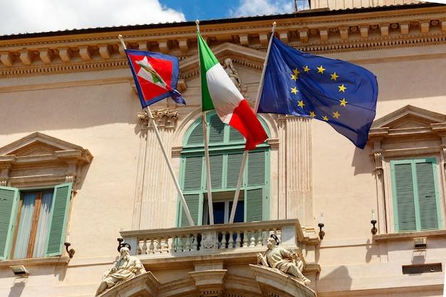 Bella grande bandiera sventolante dell'unione europea, bandiera dell'italia e stendardo presidenziale italiano sul balcone del palazzo del quirinale, roma, italia.