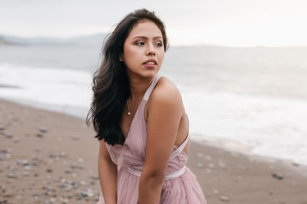 Bella ragazza latina con il lungo bastone nero in posa in un bellissimo tramonto sulla spiaggia vestita con un abito rosa da balletto