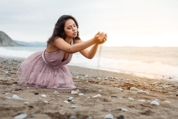 Bella ragazza latina con il lungo bastone nero in posa in ginocchio sul pavimento e giocando con la sabbia tra le mani su un bellissimo tramonto sulla spiaggia vestita con un abito da ballo rosa