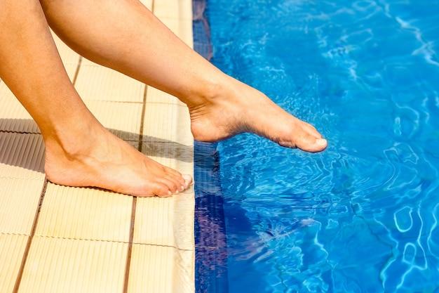 Belle gambe di una ragazza vicino a una piscina sulla superficie del mare