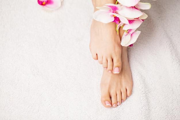 Belle gambe di una donna con una fresca pedicure francese