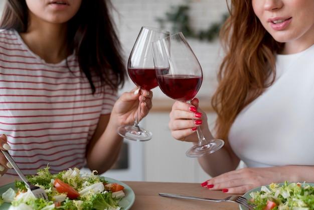 Bella coppia lesbica che fa il tifo con dei bicchieri di vino