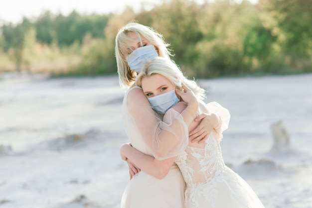 Belle coppie lesbiche che camminano sulla sabbia lungo una riva del fiume il giorno delle nozze