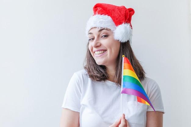 Bella ragazza lesbica in cappello rosso di babbo natale con bandiera arcobaleno lgbt isolata su sfondo bianco che sembra felice ed eccitata. ritratto di giovane donna gay pride. buone vacanze di natale e capodanno.