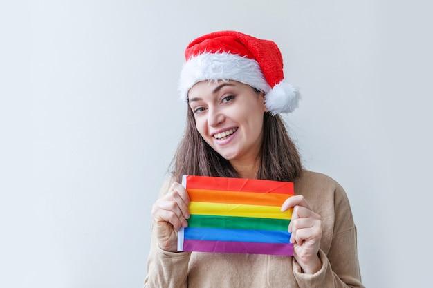 Bella ragazza lesbica in cappello rosso di babbo natale con bandiera arcobaleno lgbt isolato su priorità bassa bianca