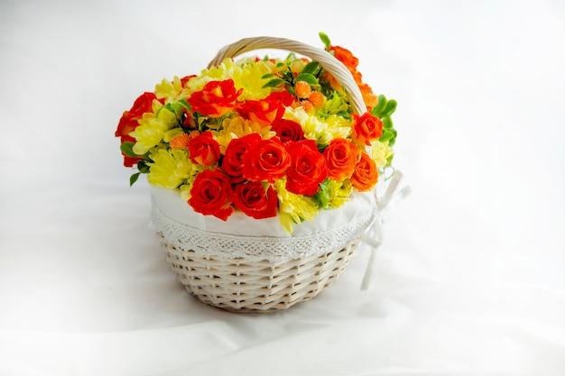 Bellissimo cesto di vimini leggero con fiori gialli e rossi per le vacanze di primavera congratulazioni
