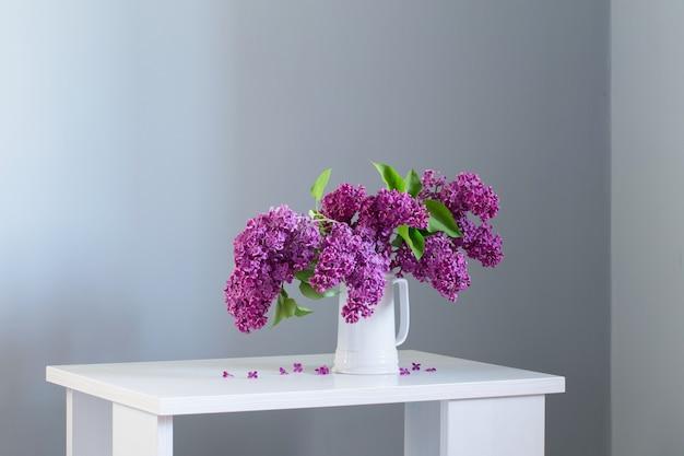 Bellissimi fiori lilla in una brocca bianca su un tavolo di legno bianco